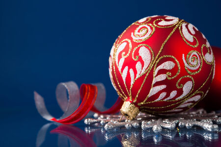 Red and silver christmas ornaments on dark blue xmas background with space for text