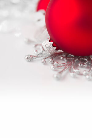 Red and silver xmas ornaments on bright holiday background. Merry christmas!