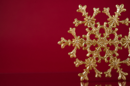 Christmas golden snowflake on dark red background with space for text. Xmas holiday theme.