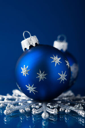 Silver and blue christmas ornaments on dark blue background with space for text. Xmas theme. photo