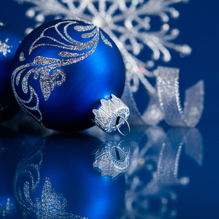 Blue and silver christmas ornaments on dark blue xmas background with space for text photo