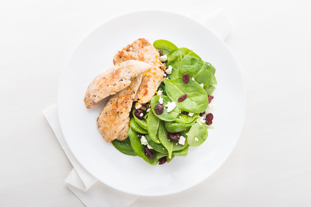 Chicken with spinach salad on white wooden background top view. Healthy food. Foto de archivo