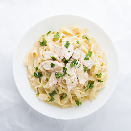 Pasta fettuccine alfredo with chicken, parmesan and parsley on white background top view. Italian cuisine.