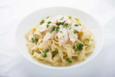alfredo: Pasta fettuccine alfredo with chicken, parmesan and parsley on white background close up. Italian cuisine.