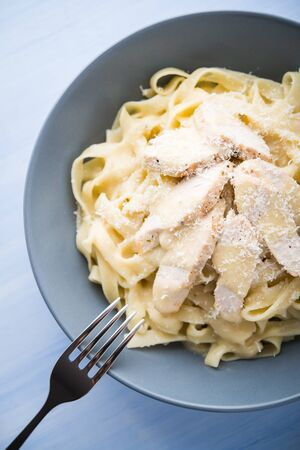 alfredo: Pasta fettuccine alfredo with chicken and parmesan on blue wooden background top view. Italian cuisine.