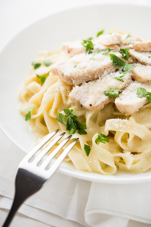 Pasta fettuccine alfredo with chicken, parmesan and parsley on white background close up. Italian cuisine.