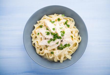 Pasta fettuccine alfredo con pollo, parmigiano e prezzemolo su legno blu sfondo vista superiore. Cucina italiana. Archivio Fotografico