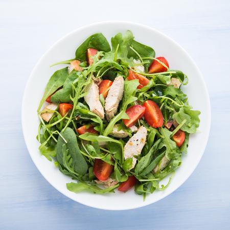 ensalada tomate: ensalada fresca con pollo, tomate y verduras (espinacas, rúcula) en azul Vista superior de fondo de madera. Comida sana.