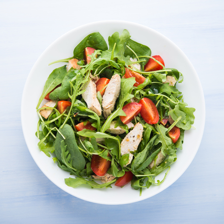 Fresh salad with chicken, tomato and greens (spinach, arugula) on blue wooden background top view. Healthy food. 免版税图像