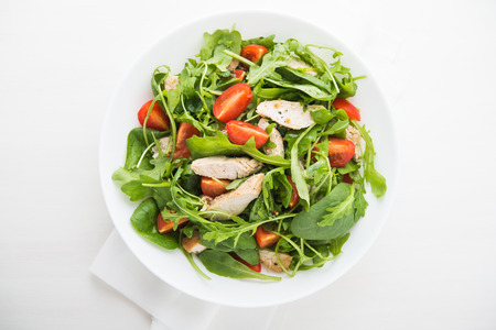 restaurant food: Fresh salad with chicken, tomato and greens (spinach, arugula) top view. Healthy food.