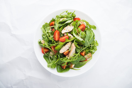 tomate ensalada: Fresh salad with chicken, tomato and greens (spinach, arugula) on white background top view. Healthy food.