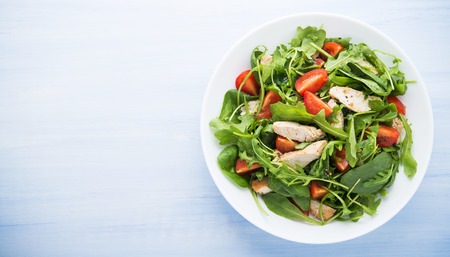 Fresh salad with chicken, tomato and greens (spinach, arugula) on blue wooden background top view. Healthy food. Space for text.