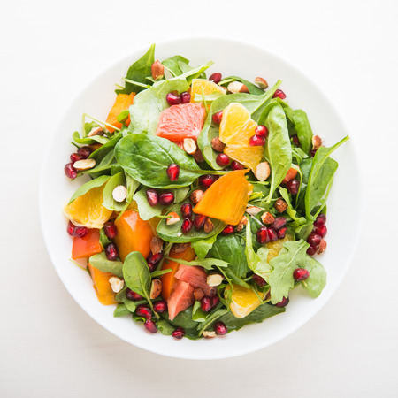 Fresh salad with fruits and greens on white background top view. Healthy food. Stock Photo