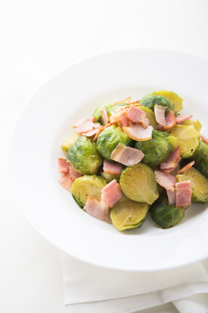 Brussels sprouts with bacon on white background.