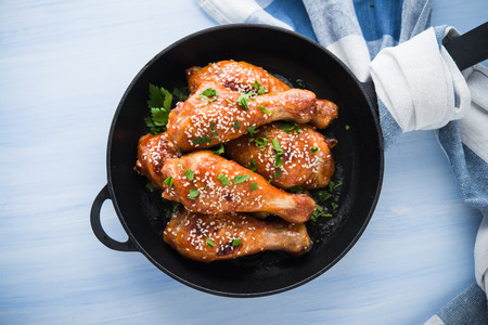 Baked spicy chicken legs with sesame and parsley in cast iron frying pan on blue wooden background top view. Asian food.