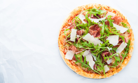 Pizza with prosciutto (parma ham), arugula (salad rocket) and parmesan on white background top view. Italian cuisine. Space for text.