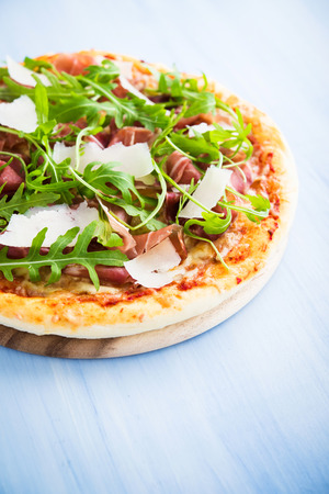 masa: Pizza con jamón (jamón de Parma), rúcula (cohete ensalada) y parmesano en el fondo de madera azul de cerca. Cocina italiana.