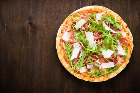 Pizza con prosciutto crudo (prosciutto di Parma), rucola (insalata di rucola) e parmigiano su fondo in legno scuro vista superiore. Cucina italiana. Spazio per il testo