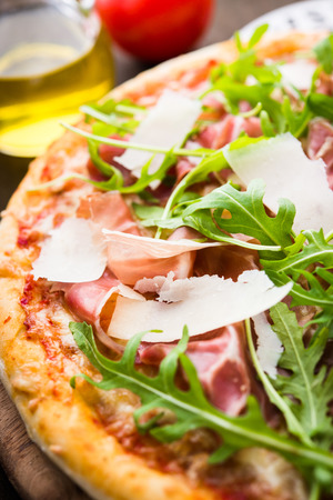 Pizza with prosciutto (parma ham), arugula (salad rocket) and parmesan on dark wooden background close up. Italian cuisine.