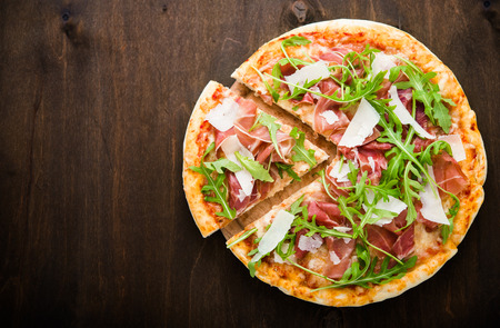 Sliced pizza with prosciutto (parma ham), arugula (salad rocket) and parmesan on dark wooden background top view. Italian cuisine. Space for text.