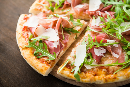 Sliced pizza with prosciutto (parma ham), arugula (salad rocket) and parmesan on dark wooden background close up. Italian cuisine.