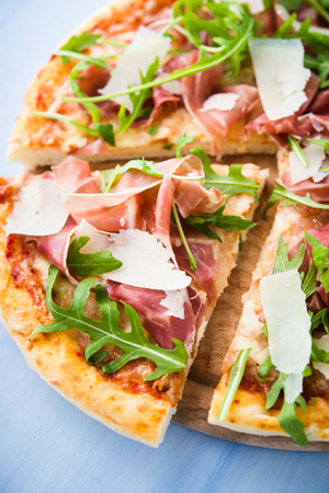 Sliced pizza with prosciutto (parma ham), arugula (salad rocket) and parmesan on blue wooden background close up. Italian cuisine.