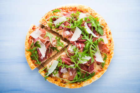 Sliced pizza with prosciutto (parma ham), arugula (salad rocket) and parmesan on blue wooden background top view. Italian cuisine.