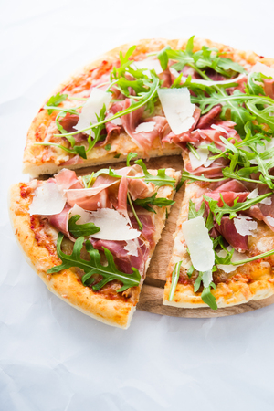 Sliced pizza with prosciutto (parma ham), arugula (salad rocket) and parmesan on white background close up. Italian cuisine. Stock Photo