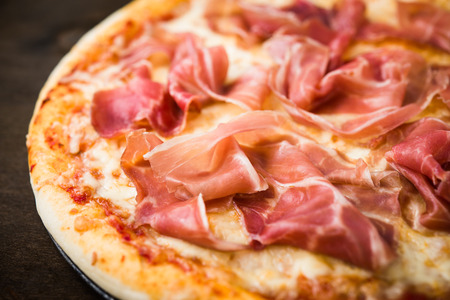 Pizza with prosciutto (parma ham) on dark wooden background close up. Italian cuisine.