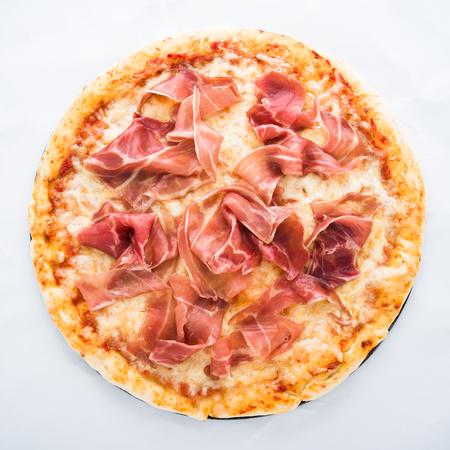 Pizza with prosciutto (parma ham) on white background top view. Italian cuisine.