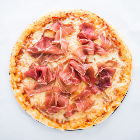 Pizza with prosciutto (parma ham) on white background top view. Italian cuisine.