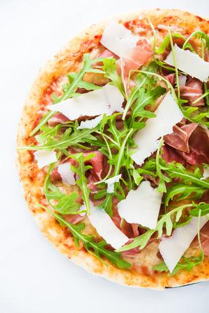 Pizza with prosciutto (parma ham), arugula (salad rocket) and parmesan top view. Italian cuisine.