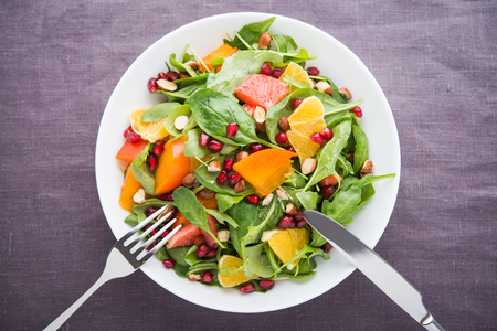 Fresh salad with fruits and greens on dark canvas background top view. Healthy food.
