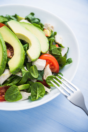 Fresh salad with chicken, tomatoes, spinach and avocado on blue wooden background close up. Healthy food.