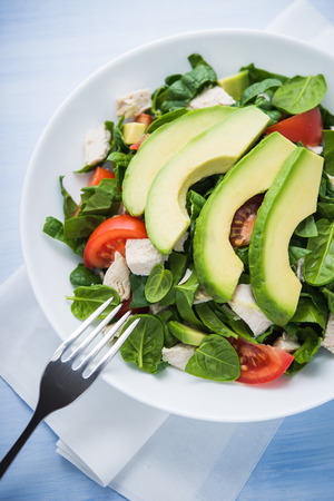 Fresh salad with chicken, tomatoes, spinach and avocado on blue wooden background top view. Healthy food.