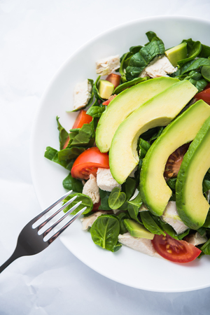 Fresh salad with chicken, tomatoes, spinach and avocado on white background top view. Healthy food. Stock Photo
