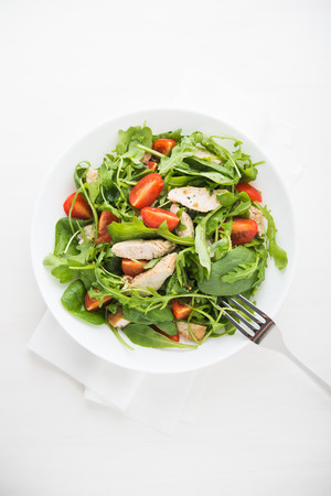 tomate ensalada: Fresh salad with chicken, tomato and greens (spinach, arugula) top view. Healthy food.