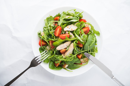 Fresh salad with chicken, tomato and greens (spinach, arugula) on white background top view. Healthy food.