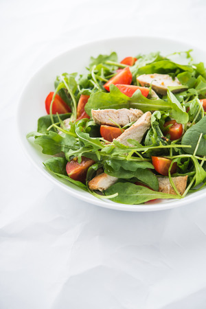 Fresh salad with chicken, tomato and greens (spinach, arugula) on white background close up. Healthy food.
