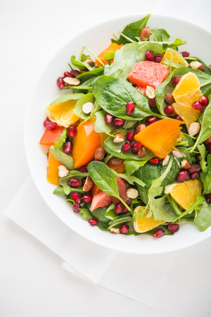 Fresh salad with fruits and greens on white background top view. Healthy food. Foto de archivo