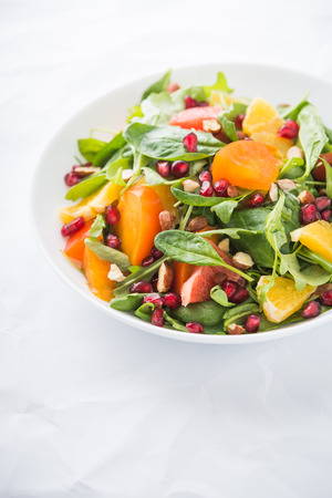 Fresh salad with fruits and greens on white background close up. Healthy food.