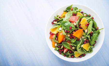 Fresh salad with fruits and greens on blue wooden background top view. Healthy food. Space for text. Stock Photo