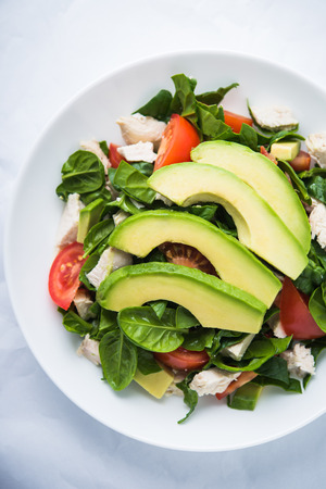 Fresh salad with chicken, tomatoes, spinach and avocado on white background top view. Healthy food. Foto de archivo