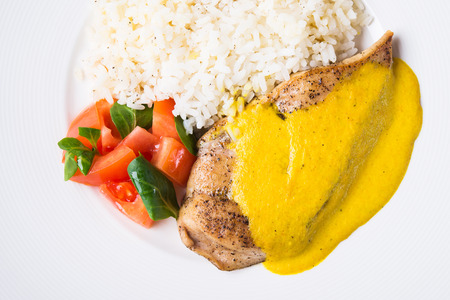 Chicken curry with white rice and vegetables in a white plate top view.