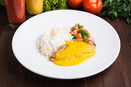 Chicken curry with white rice and vegetables in a plate on dark wood background.