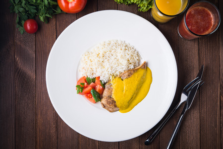 Chicken curry with white rice and vegetables in a plate on dark wood background top view.