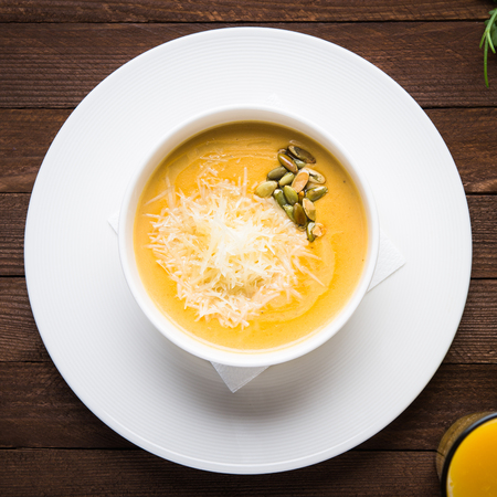 Creamy pumpkin soup with sids and parmesan on dark wooden background top view. Stock Photo