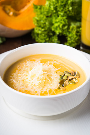 Creamy pumpkin soup with sids and parmesan on dark wooden background close up.