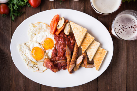English breakfast (fried eggs, beans, roasted bacon, sausages and vegetables) on dark wood background top view.