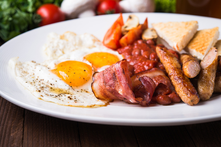 English breakfast (poached eggs, beans, roasted bacon, sausages and vegetables) close up. Stock Photo